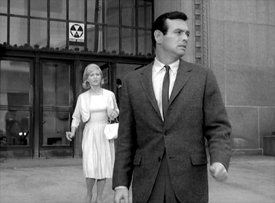 David Jansen (The Fugitive) and Susan Clark outside a building marked by a National Fallout Shelter Sign 'where 50 or more persons can be sheltered from radioactive fallout resulting from a nuclear attack'