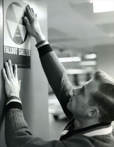 Mounting a fallout shelter sign... circa 1962