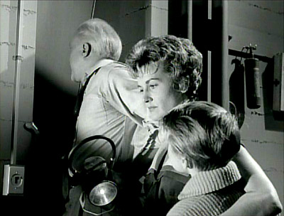 The family anxiously waits as the neighbors attack their shelter door in Rod Serling's 'The Shelter' epsiode of The Twilight Zone, first broadcast September 29, 1961